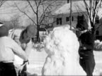 1945 Black and white Medium shot girl packing snow on body of snow man / younger boy hands older boy snowball for the head / AUDIO
