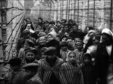 1945 black and white medium shot Jewish children being led past barbed wire by nuns at Auschwitz / Poland