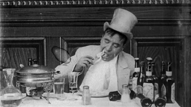 1906 black and white medium shot man (Jack Brawn) eating Welsh Rarebit / doing 'spit take' / 'Dream of a Rarebit Fiend'