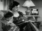 1956 black and white medium shot mother sitting in chair with arm around young son  / reading book to boy / AUDIO