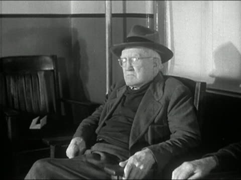 1940S black and white medium shot pan five elderly men sitting in room at nursing home