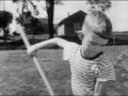 1956 black and white medium shot pan Sulking boy raking grass and making faces / AUDIO