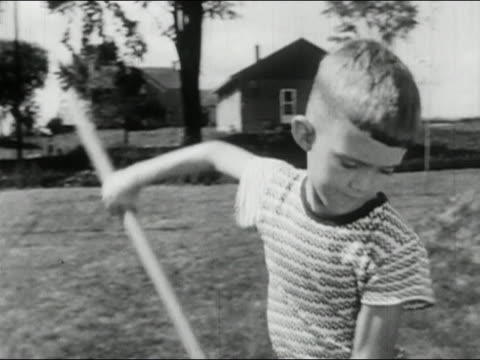 1956 black and white medium shot pan Sulking boy raking grass and making faces / AUDIO