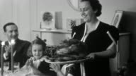 1937 black and white medium shot woman (Mrs. Saracen) carrying turkey into dining room on Thanksgiving /family applauding