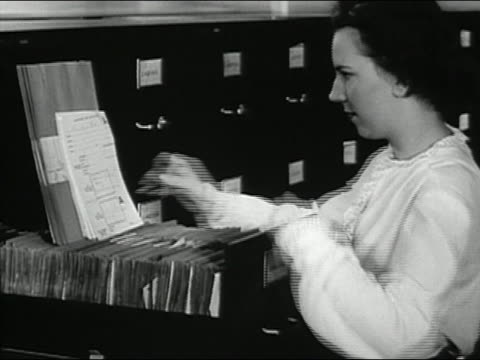 1947 black and white medium shot woman filing forms in drawer of filing cabinet / AUDIO