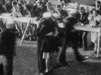 1945 black and white medium shot woman greeting and kissing returning sailor during homecoming parade / New York City