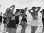 Black and white medium shot women taking exercise class led by Charles Atlas on beach