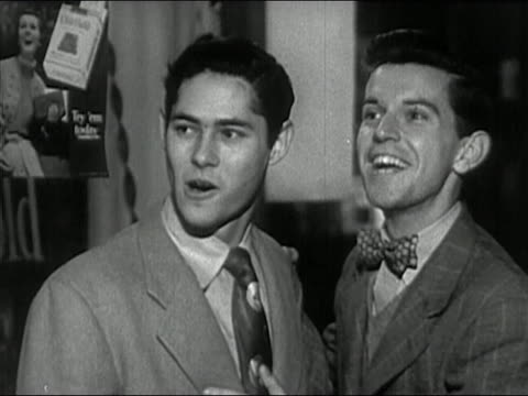 1950 black and white two teenage boys shouting and trying to get attention of girls