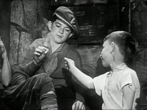 1950 black and white two young boys sharing cigarette on stoop