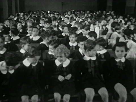 1946 black and white wide shot boys in school uniforms sitting in assembly hall/ pan to girls on other side / Italy