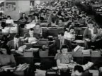 1947 black and white wide shot men and women working at desks in huge open plan office / AUDIO