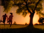 REAR VIEW SILHOUETTE Black boy + girl holding hands + running towards tree at sunset