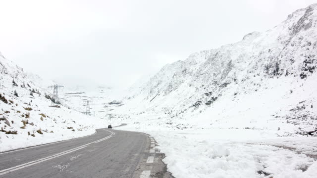 Black car driving along Hairpin curve between snowy mountains