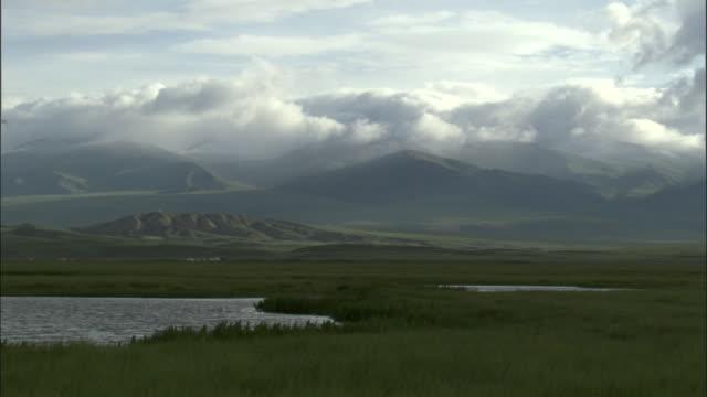 Black clouds over hills and lake, Bayanbulak grasslands.