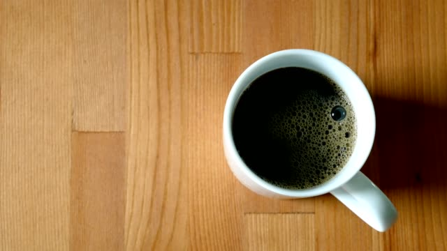 black coffee pouring from bottle into a cup on wooden table