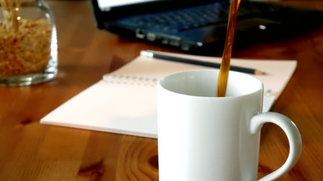 Black coffee pouring from bottle into a cup on wooden table with office supplies on background