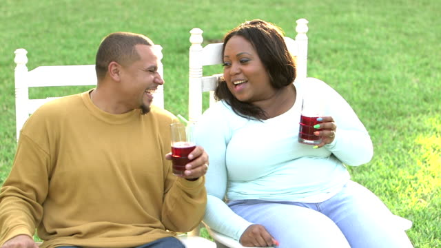 Black couple sitting outdoors, drinking refreshments