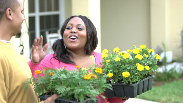 Black couple talking, with potted flowers ready to plant