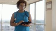 Black doctor walking and using digital tablet in lobby