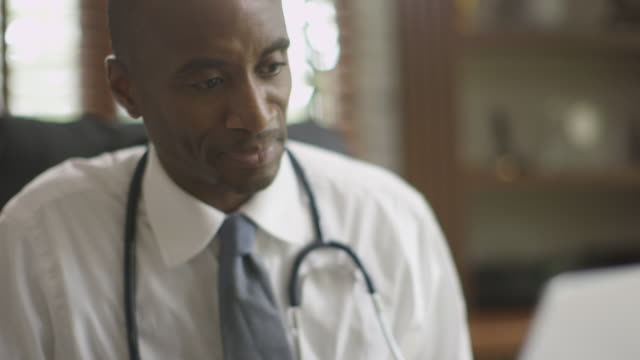 Black doctor working on laptop in office