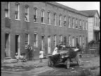 B/W 1927 Black family exiting rowhouse + piling into car as man cranks engine / educational