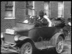 B/W 1927 Black family piling into car driving away / educational