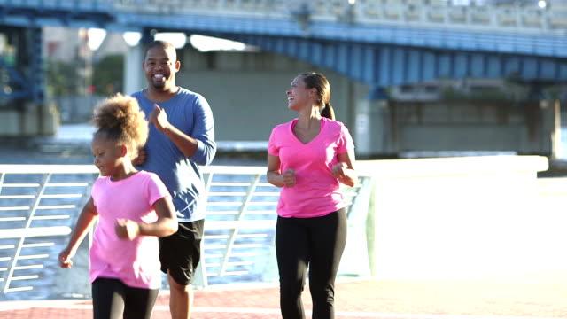 Schwarze Familie mit zwei Kindern, die sich fit halten, Powerwalking