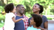 Black family with two children laughing together
