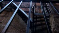 Black fire escape on brick building black barred fencing FG