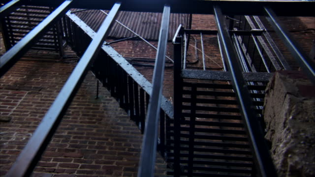 Black fire escape on brick building black barred fencing FG