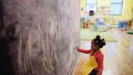 Black girl drawing on chalkboard wall at daycare