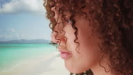 Black girl looks off at the Caribbean ocean