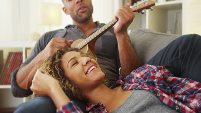 Black girlfriend enjoying being serenaded to by boyfriend