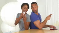 Black girlfriend shows boyfriend photo on mobile phone