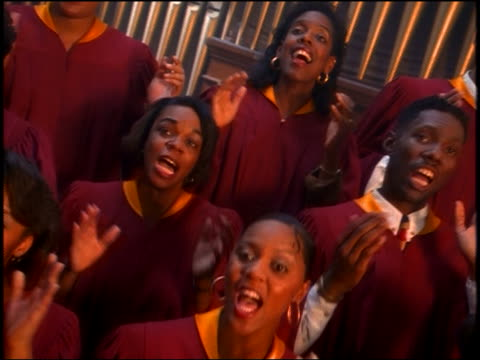 CANTED PAN Black gospel choir in robes singing + clapping in church