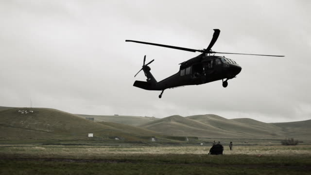 Black Hawk dropping cargo and flying off.