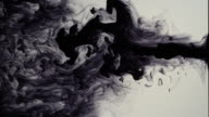Black ink squirting and dispersing in turbulent pattern of swirls