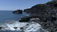 Black lava coastline with arch, aerial move