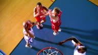 OVERHEAD Black male basketball player does reverse lay-up shot / other players moving on court