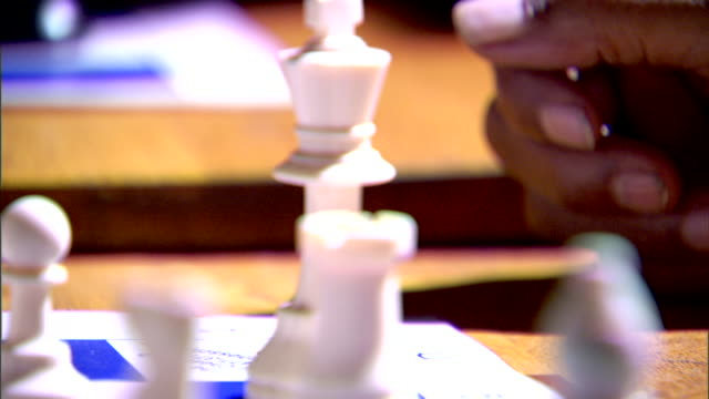 Black male hand resting behind white chess pieces CU King being guarded by pawn rook knight