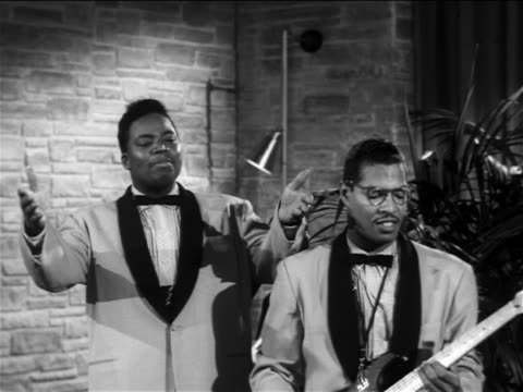 B/W 1956 Black male singer + guitarist performing 'Over + Over Again' on small stage / The Moonglows
