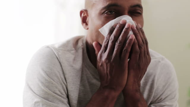 Black man blowing nose with tissue