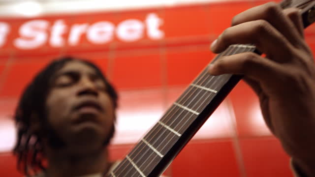 MED black man plays guitar while leaning against red wall in subway station   rack focus