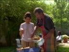 Black man serving meat on grill to 2 women in backyard BBQ