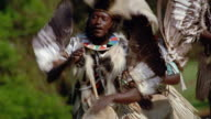 MS PAN Black men wearing tribal dress drumming + dancing in ceremony / Kenya