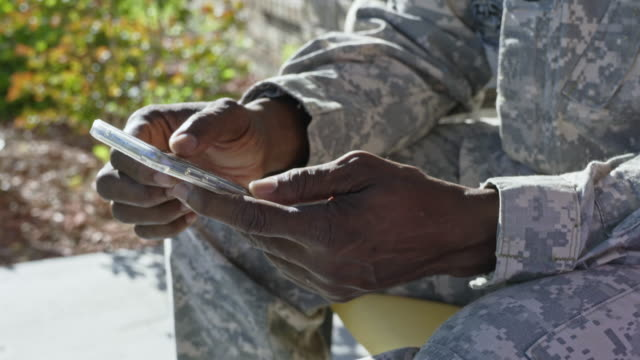 Black military man texting on cell phone