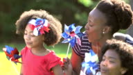 Black mother and children playing on American holiday