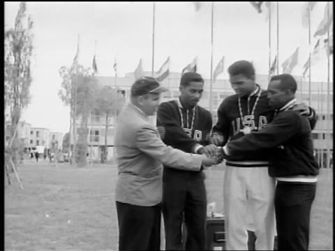 Black Olympic medalists kissing medals / Rome / documentary