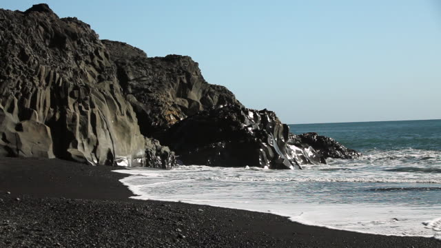 MS Black rock formations surround black rock beach and waves crashing up on shore / VIK, Vestur-Skaftafellssysla, Iceland