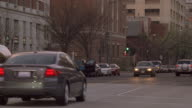 TS A black sedan maneuvering traffic on a busy downtown street / Washington, D.C., United States